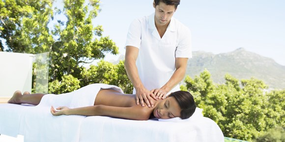Woman receiving massage on patio at spa
